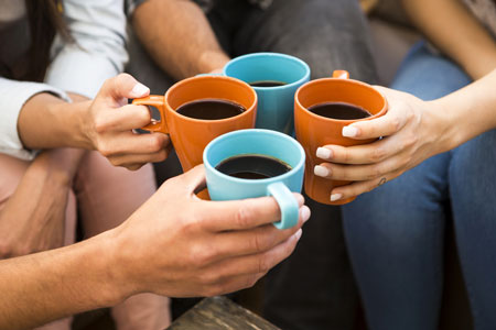 Four Individuals sitting in a circle hold coffee mugs together as they make a toast.