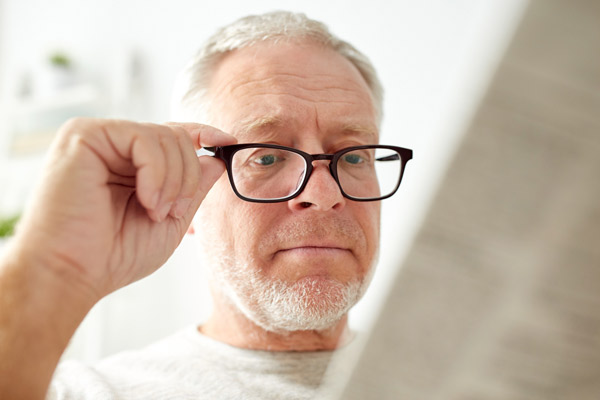 Male over the age of forty with Presbyopia tries on eyeglasses.