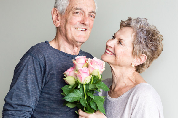 Smiling couple over the age of 60 holds a bouquet of flowers.