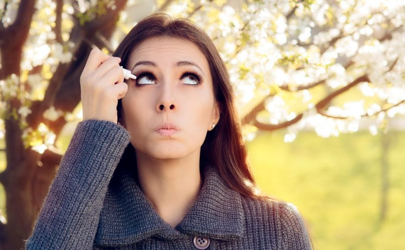 Young woman with allergies and itchy eyes stands outside while putting eye drops in her eyes.